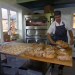 Helge tar ut bröd ur ugnen gårdsbageri